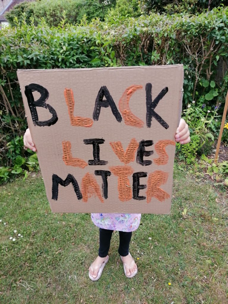 Photo of daughter holding our own sign that reads Black Lives Matter in orange and black.