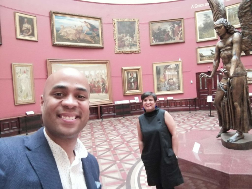Photo of Sara and Zak standing in the main hall at Birmingham Museum & Art Gallery with paintings in the background