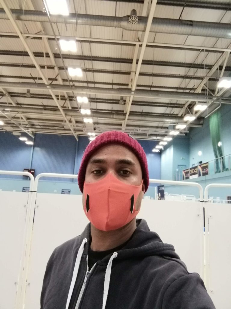 Photo of me standing at the entrance to the vaccination centre to get my first dose of Pfizer covid-19 vaccination. I'm wearing a beige beanie hat, navy hoodie and orange U-mask.